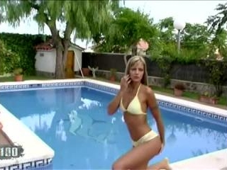 Little blonde removing her clothes by the pool