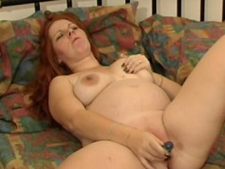 Redhead pleasures her pregnant pussy with a toy