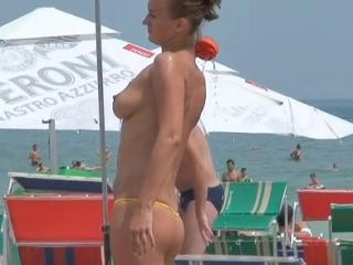 The beautiful topless bikini chick is on the beach