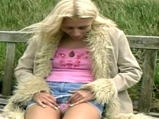 Tall blonde shows off outside on a bench