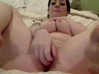 Tattooed chick fucks her smooth pussy