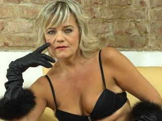 Naughty cougar fingering herself on the couch
